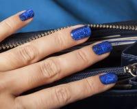 Pretty fingers, deep blue manicure close up with. Purse, luxury design indigo pattern stock photos