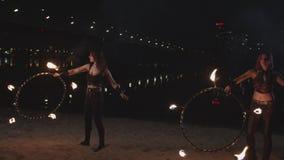 Pretty firegirls working with fire hoops outdoor stock footage