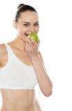Pretty fit trendy woman eating fresh green apple Stock Images