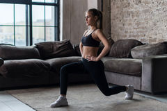 Pretty fit woman doing frontal lunges or squat exercise indoors in a flat.  Royalty Free Stock Image