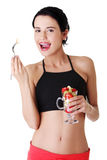 Pretty fit woman eating fruit salad Stock Photo