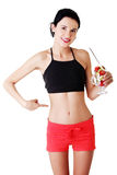 Pretty fit woman eating fruit salad Royalty Free Stock Images