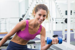 Pretty fit woman lifting blue dumbbell sitting on bench Stock Photo