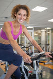 Pretty fit woman on the spin bike smiling at camera. At the gym Royalty Free Stock Image