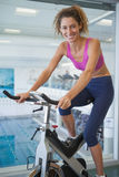 Pretty fit woman on the spin bike smiling at camera. At the gym Royalty Free Stock Photo