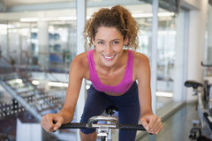 Pretty fit woman on the spin bike smiling at camera. At the gym Royalty Free Stock Photography