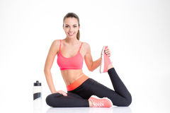 Pretty fitness girl with bottle of water stretching her leg Royalty Free Stock Image