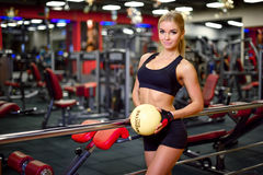 Pretty fitness girl holding a ball, in the gym, looking right, the background beautifully blurred Stock Image