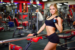 Pretty fitness girl holding a jump rope in the gym, looking right, the background beautifully blurred Stock Image
