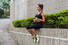 Pretty fitness girl resting after jogging, sitting on parapet, drinking water and preparing for running. Stock Photos