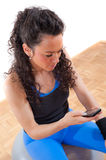 Pretty fitness girl taking a break with cellphone. Young, attractive brunette, sitting on a exercising ball, talking on a cellphone during a short break Stock Images