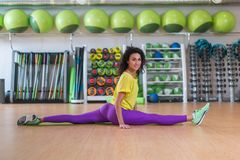 Pretty fitness model in sportswear doing front split in gym, stretching her legs, looking at camera and smiling. Stock Photography