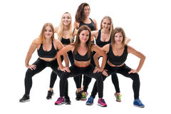 Pretty fitness trainers in black tops and leggings. Young and pretty fitness trainers in black tops, leggings and bright sneakers posing in group in studio Royalty Free Stock Photography