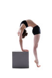 Pretty flexible girl posing on cube in studio Royalty Free Stock Photos