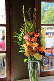 Pretty floral arrangement at wood framed windows Stock Photo