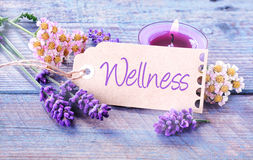 Pretty floral Wellness background. With fresh scented lavender and dainty inflorescences around a label with the script - Wellness - leaning against a burning Royalty Free Stock Image