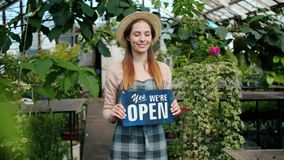 Pretty florist standing in greenhouse holding open sign looking at camera. Pretty florist young lady in apron and hat is standing in greenhouse holding we are stock video