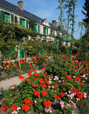 Pretty Flowers and Home. Photo of claude monet's home in the background and red flowers in the foreground in france. Claude Monet was a french impressionist stock image