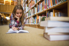 Pretty focused student lying on library floor reading book Stock Image