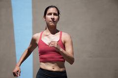 Pretty, focused woman runs to keep in shape. Stock Image