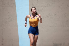 Pretty, focused woman runs to keep in shape. Royalty Free Stock Image