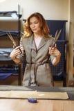 Pretty focused young woman fashion designer cutting grey fabric in studio royalty free stock photos
