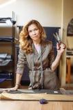 Pretty focused young woman fashion designer cutting grey fabric in studio stock photo
