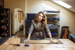 Pretty focused young woman fashion designer cutting white fabric in studio stock photo