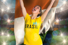 Pretty football fan in brasil t-shirt holding ivory coast flag Stock Photography