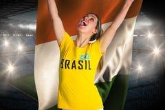 Pretty football fan in brasil t-shirt holding ivory coast flag Stock Photography
