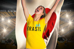 Pretty football fan in brasil t-shirt holding japan flag Stock Photo