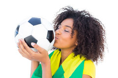 Pretty football fan with brazilian flag kissing ball Royalty Free Stock Photography