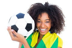 Pretty football fan with brazilian flag smiling at camera Stock Image