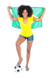Pretty football fan holding brazilian flag cheering at camera Stock Photography