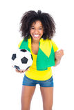 Pretty football fan holding brazilian flag cheering at camera Royalty Free Stock Photos