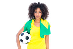 Pretty football fan holding brazilian flag looking at camera Stock Photo