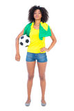 Pretty football fan holding brazilian flag looking at camera Royalty Free Stock Images