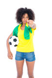 Pretty football fan holding brazilian flag pointing at camera Stock Photo