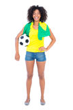 Pretty football fan holding brazilian flag smiling at camera Royalty Free Stock Photo