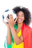 Pretty football fan with portugal flag holding ball Stock Photos