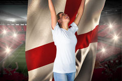 Pretty football fan in white cheering holding england flag Royalty Free Stock Photo
