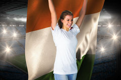 Pretty football fan in white cheering holding ivory coast flag Royalty Free Stock Image