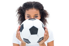Pretty football fan in white holding ball over face Stock Images