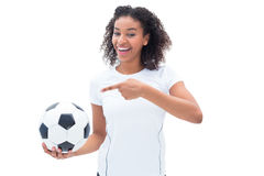Pretty football fan in white holding ball and pointing to it Stock Photography