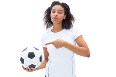 Pretty football fan in white holding ball and pointing to it Stock Image