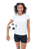 Pretty football fan in white holding ball smiling at camera Stock Photo