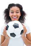Pretty football fan in white holding ball smiling at camera Stock Images