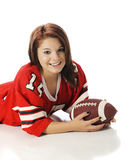 Pretty Football-Loving Teen. Closeup of a beautiful teen girl in an oversized jersey holding a football. On a white background stock photography