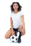Pretty football player in white holding ball looking at camera stock photos