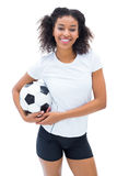 Pretty football player in white holding ball smiling at camera Stock Images